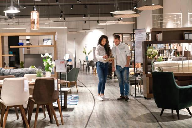 Mann im Gespräch mit einer Verkäuferin bei einem Möbelhaus – Foto