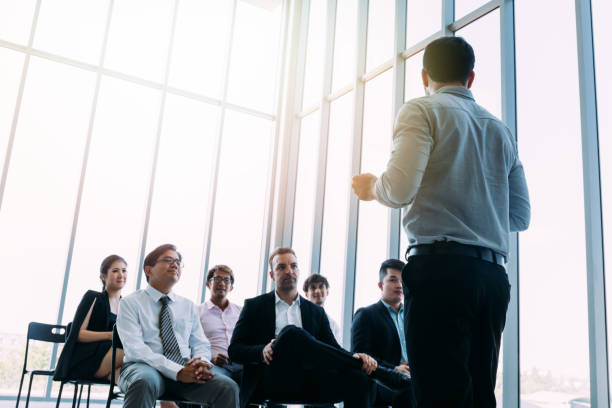 Man talking to coworkers in conference hall stock photo