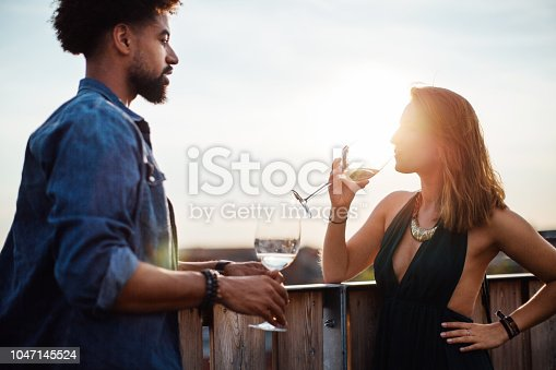 Young man talking with woman drinking wine while standing at building terrace during sunset. Multi-ethnic friends enjoying with drinks during rooftop party.