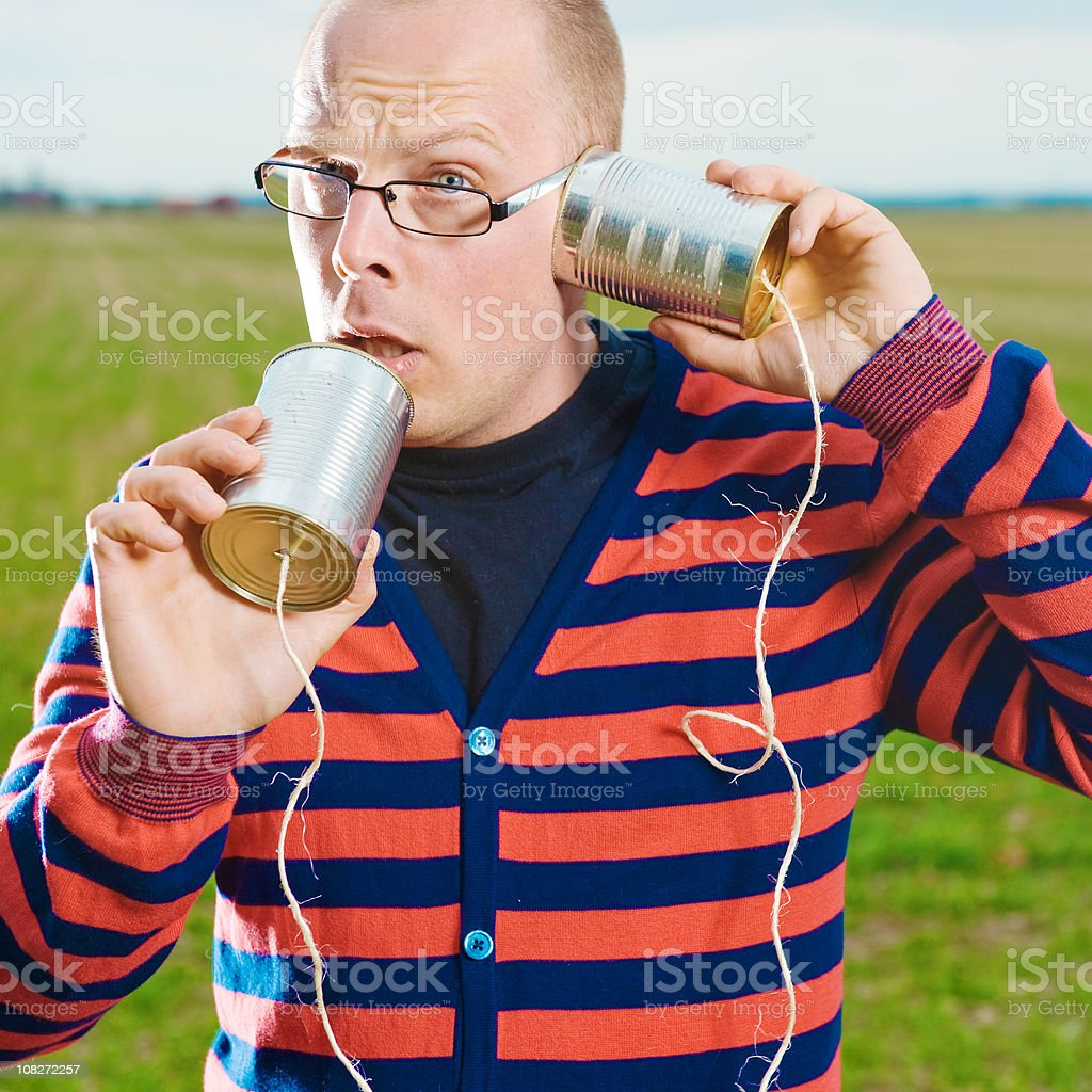 Man talking to himself on a tin can phone royalty-free stock photo