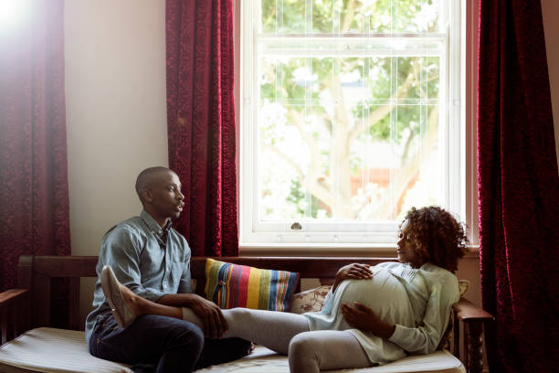 Man talking to pregnant woman at brightly lit home stock photo