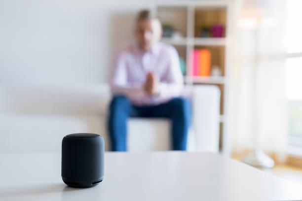 Homem falando alto-falante inteligente assistente virtual na sala de estar - foto de acervo