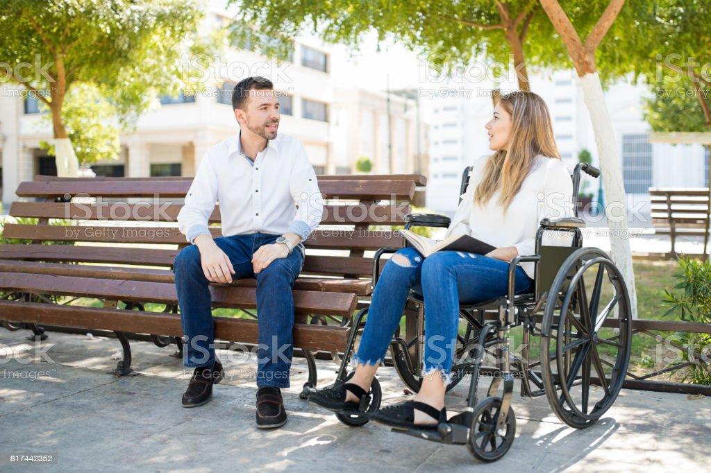Man talking to woman in wheelchair stock photo