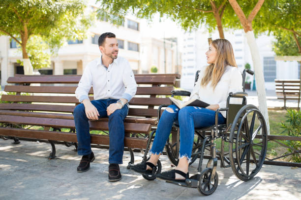 Man talking to woman in wheelchair Young man sitting in a park bench and making conversation with a woman in a wheelchair stranger stock pictures, royalty-free photos & images