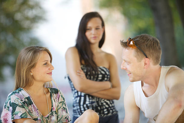 Man talking to woman while friend watches  stock photo