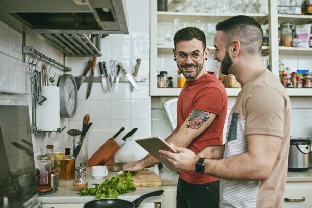 Man talking with boyfriend while preparing food stock photo