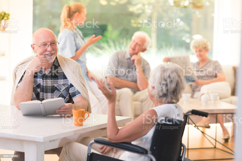 Hombre que habla con la mujer con discapacidad - Foto de stock de 60-69 años libre de derechos
