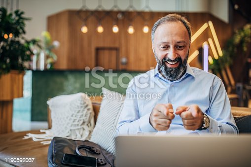 Happy men in hotel lobby talking with his family via skype while he is on his business trip