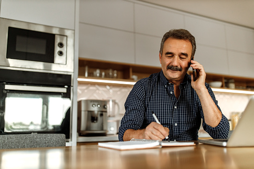 Adult man making phone call, while reading and writing some words in his notebook.