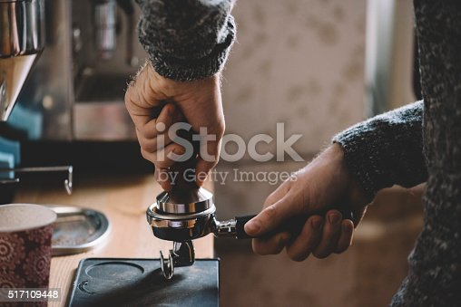 istock Man tamping fresh morning coffee 517109448