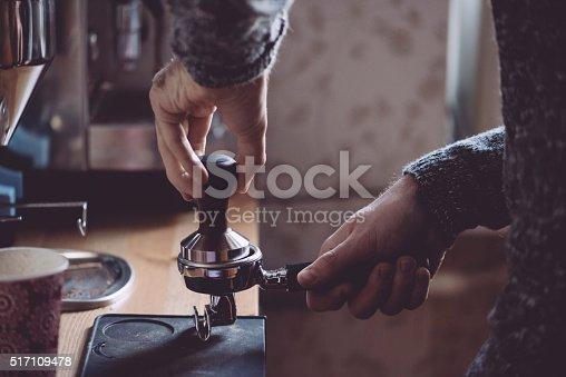 istock Man tamping fresh morning coffee 517109478