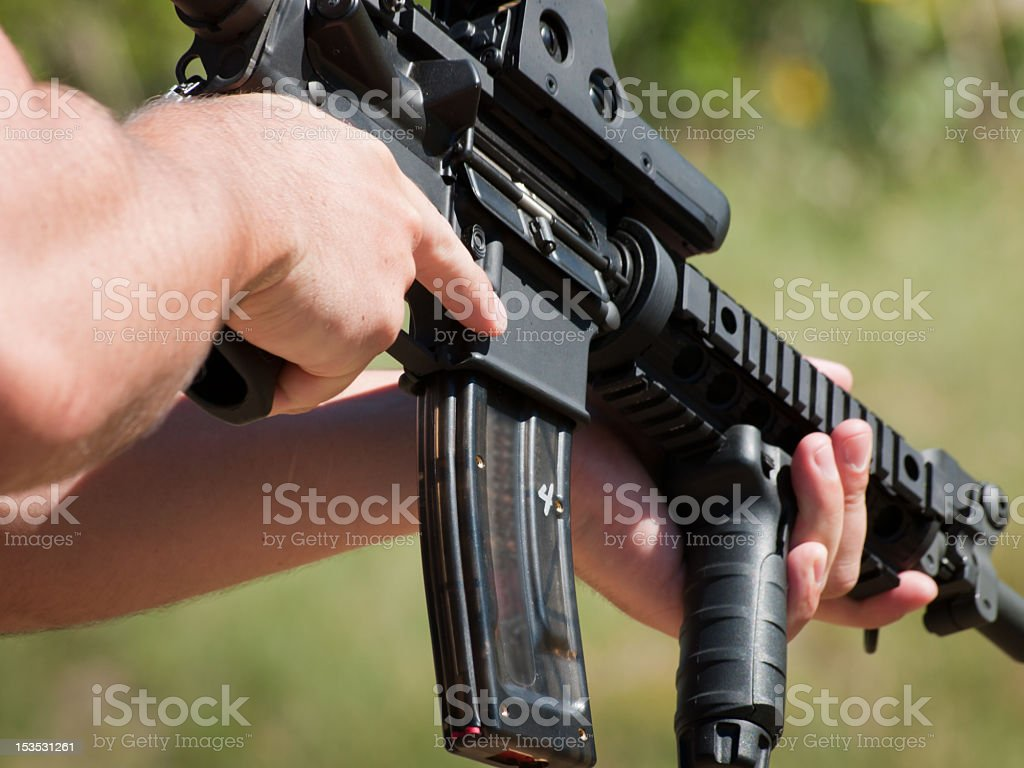 A man target shooting at a gun range stock photo