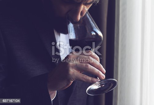 istock man tasting a glass of red wine 637167104