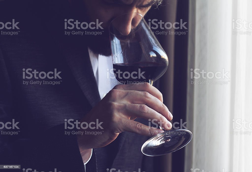 man tasting a glass of red wine stock photo