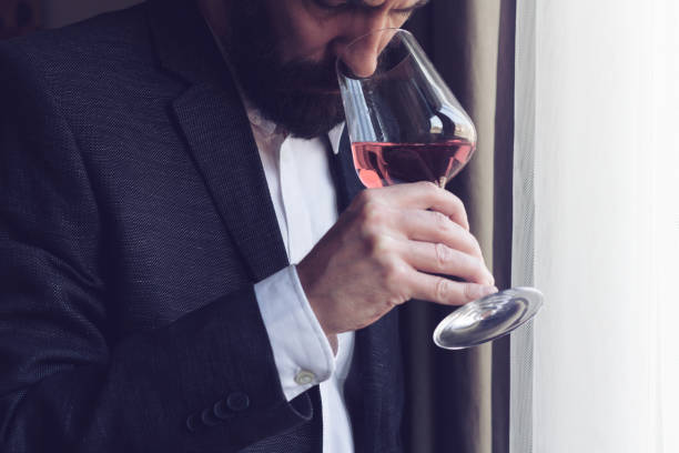 man tasting a glass of rose wine stock photo