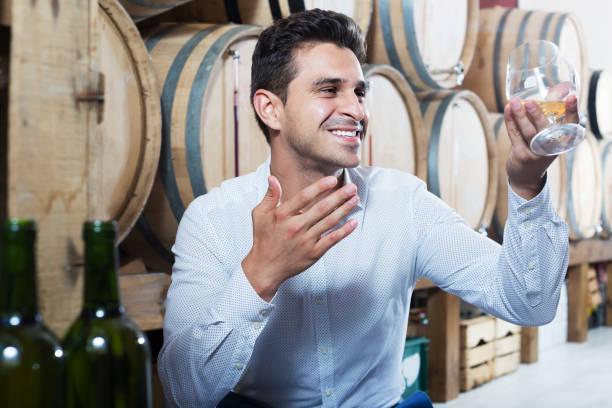 Man tasting wine in store stock photo