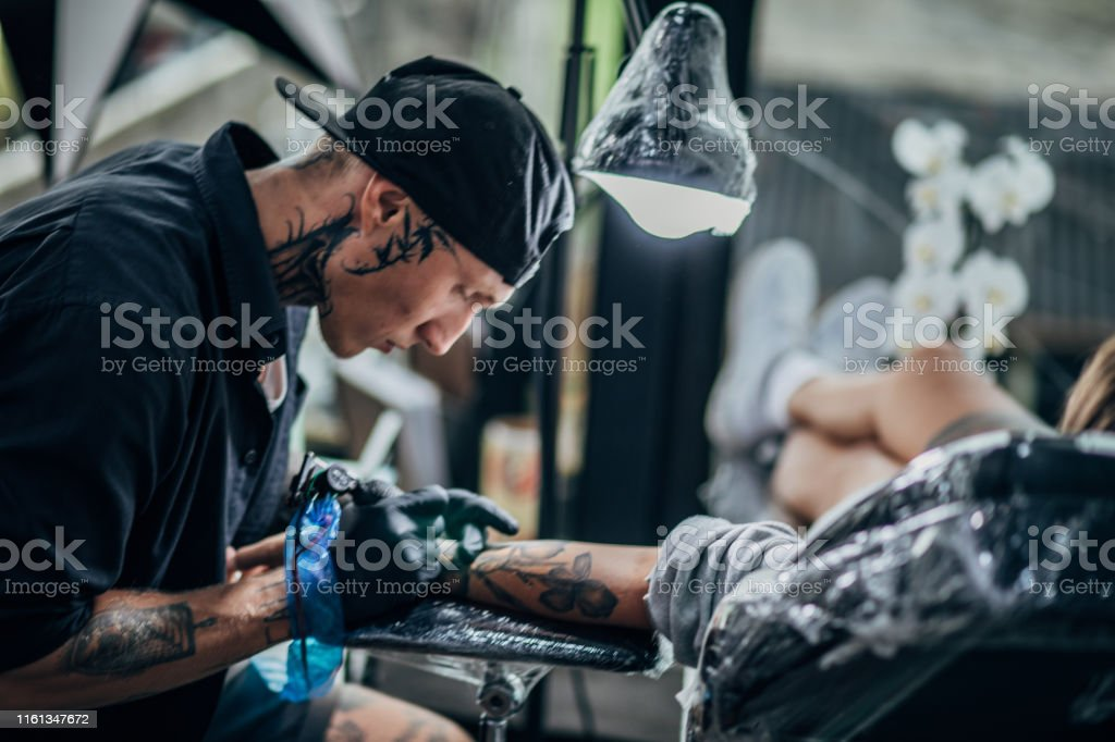 Man and woman in tattoo studio, man is tattooing a woman\'s arm.