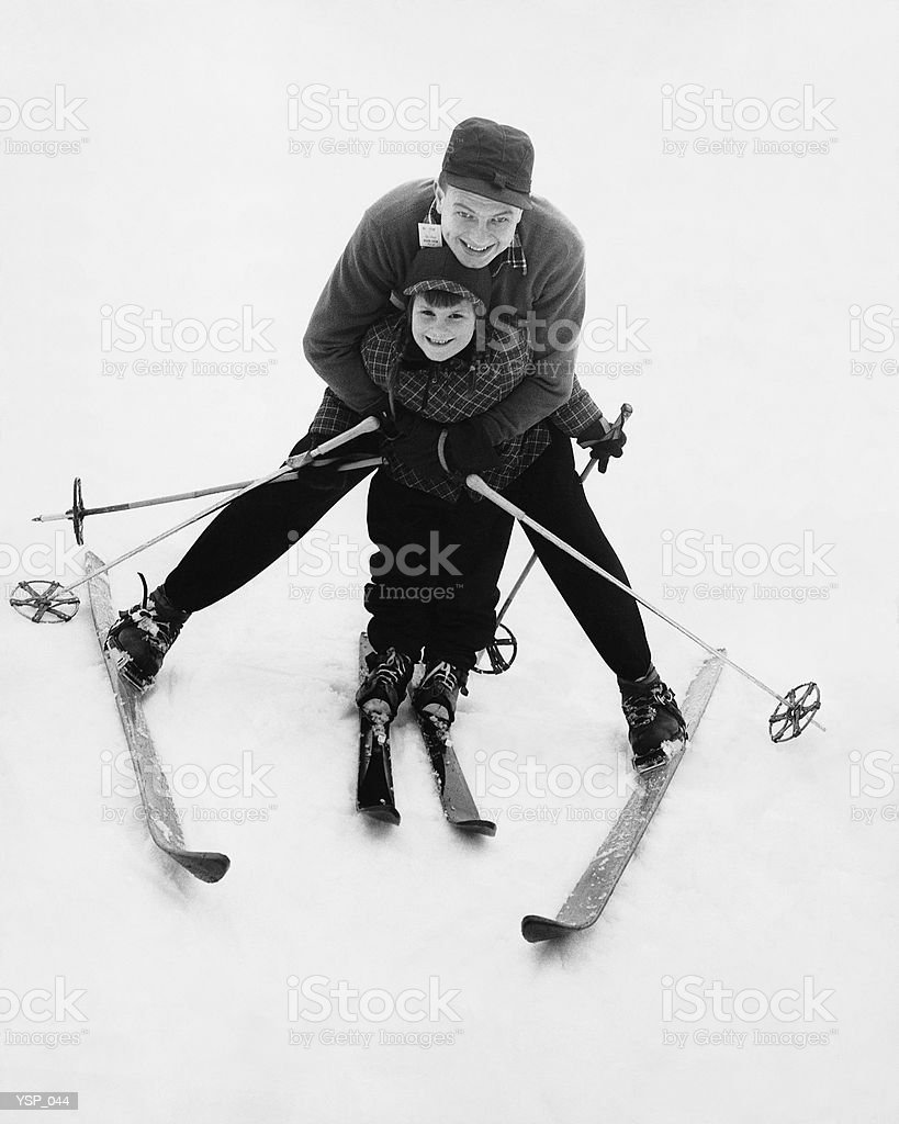 Man teaching boy to ski royalty-free stock photo