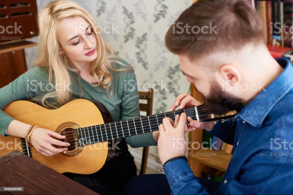 Man lehrt Freundin, Gitarre zu spielen – Foto