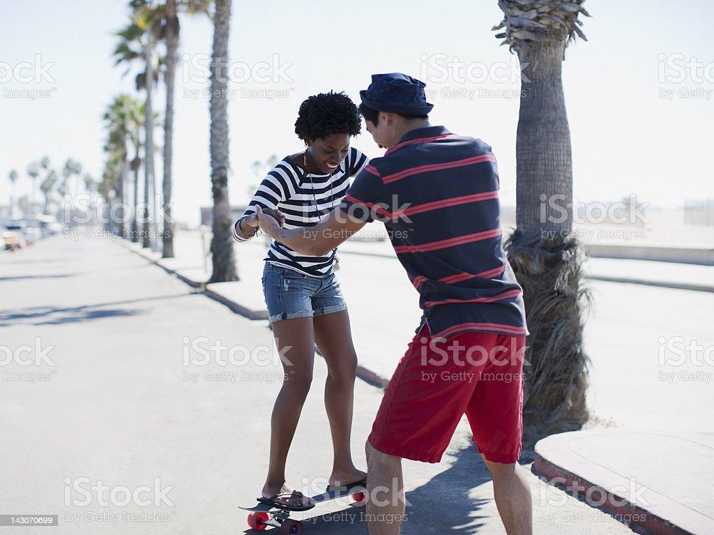 Homem dando namorada para skate - foto de acervo