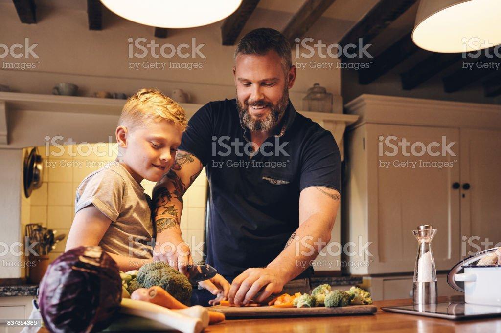 彼の息子に野菜をカットする方法を教える男 ストックフォト