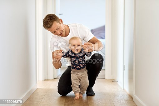 Mid adult man teaching baby son to walk in corridor. Portrait of cute little boy holding hands of father at home. They are wearing casuals.