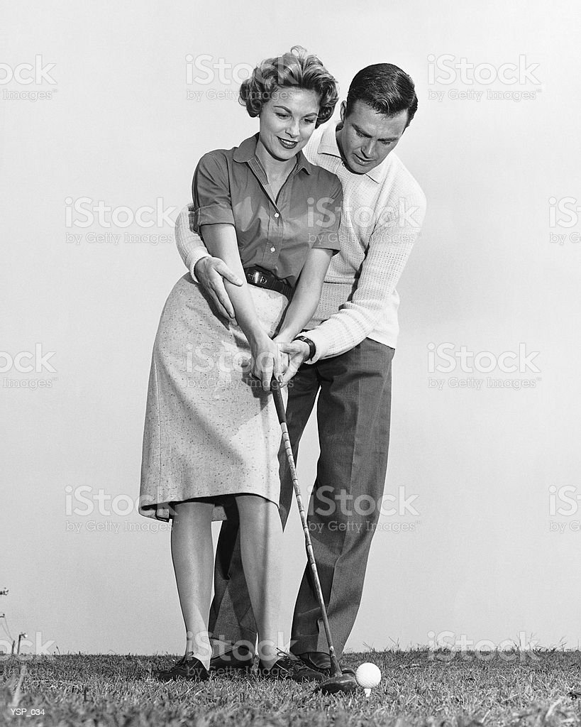 Uomo insegnare donna come battere golfball foto stock royalty-free