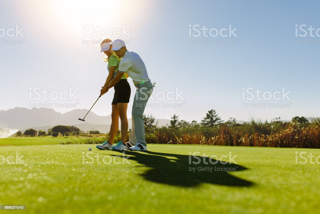 Man teaching woman to play golf on field stock photo