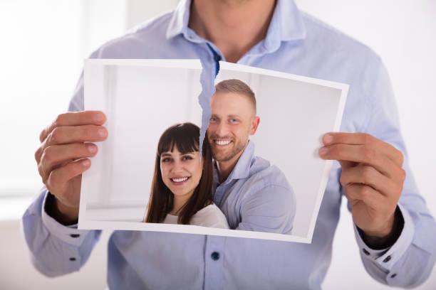 Homme déchirer la Photo du Couple de sourire - Photo