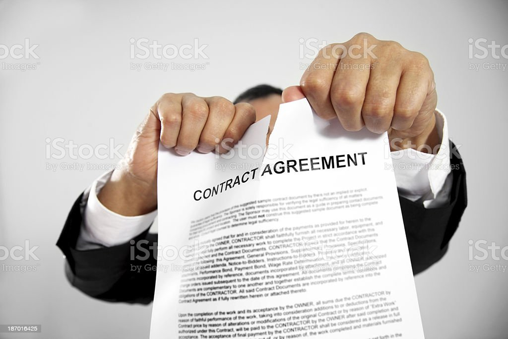 Man tearing up contract agreement stock photo