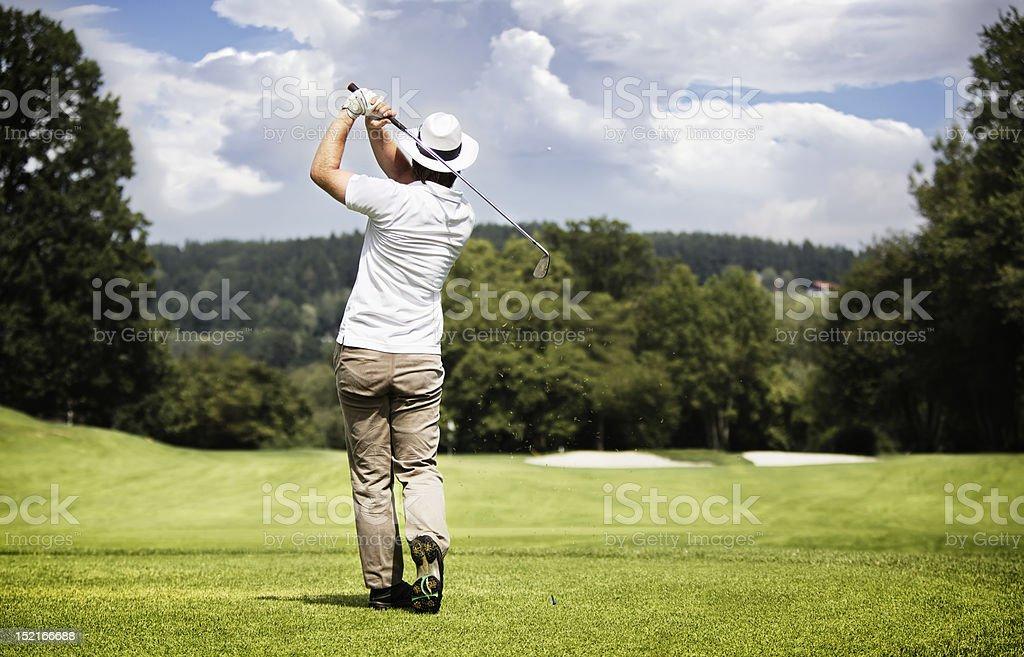 Man teeing-off golf ball. stock photo