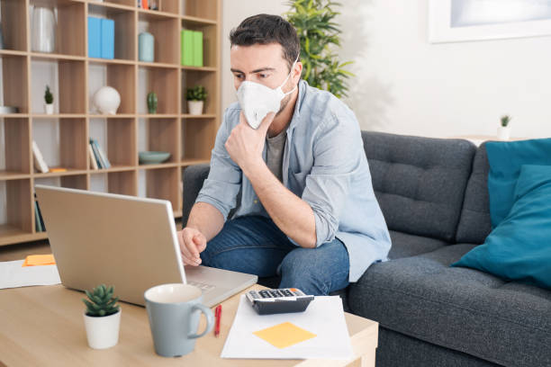 Man teleworking from home after coronavirus pandemic stock photo