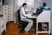 シャツ、ネクタイ、パジャマパンツを着た男性テレワーク