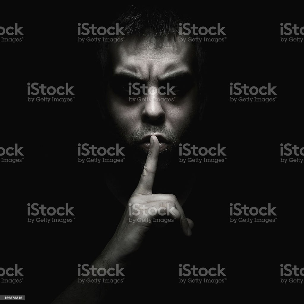 A man telling someone to be silent stock photo