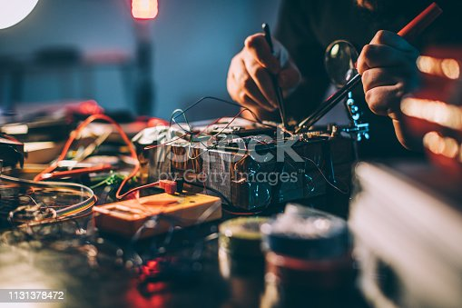One man, terrorist making a time bomb in dark workshop alone.