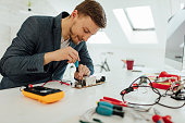 Male engineer using solder in his office. Testing a circuit board using multimeter.