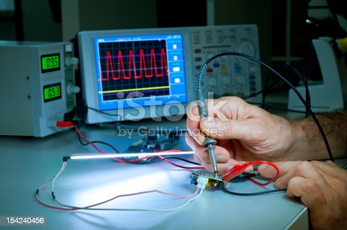 483784268 istock photo Man testing electronic equipment with machines nearby 154240456