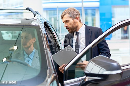 939005154 istock photo Man Testing New Car in Showroom 912116868
