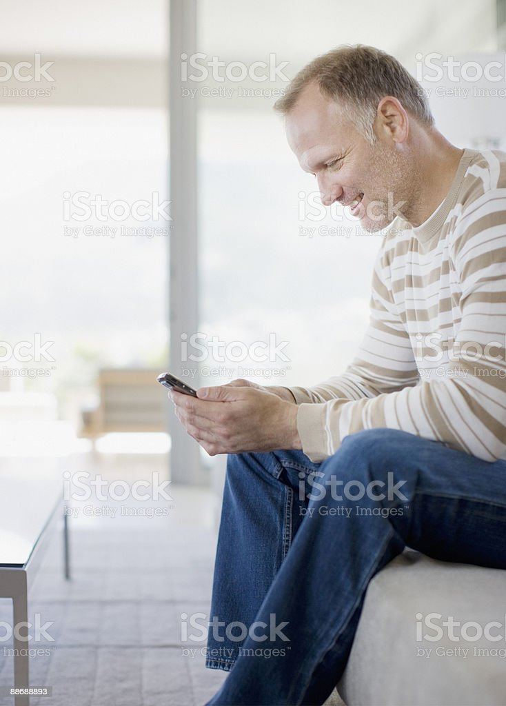 Man text messaging on cell phone in living room royalty-free stock photo