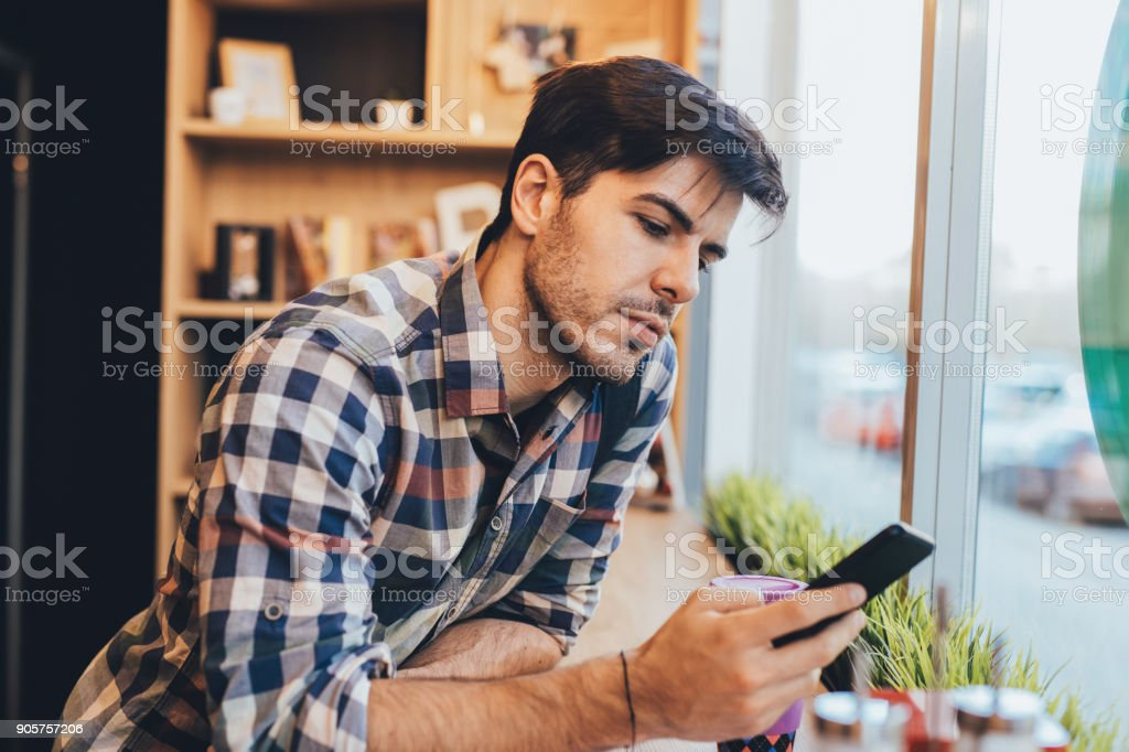 Man texting at the cafe - Royalty-free 25-29 Years Stock Photo