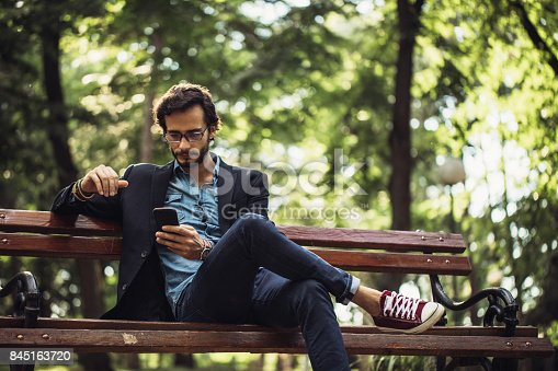 One man, sitting on park bench, using smart phone.
