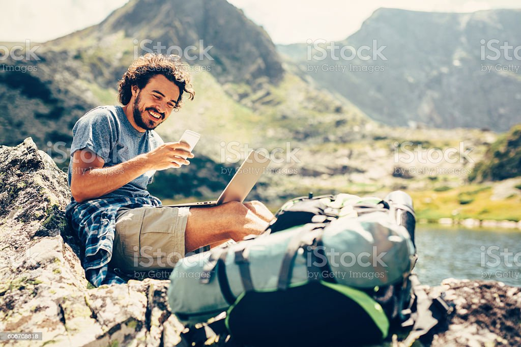 Man texting in the mountain stock photo