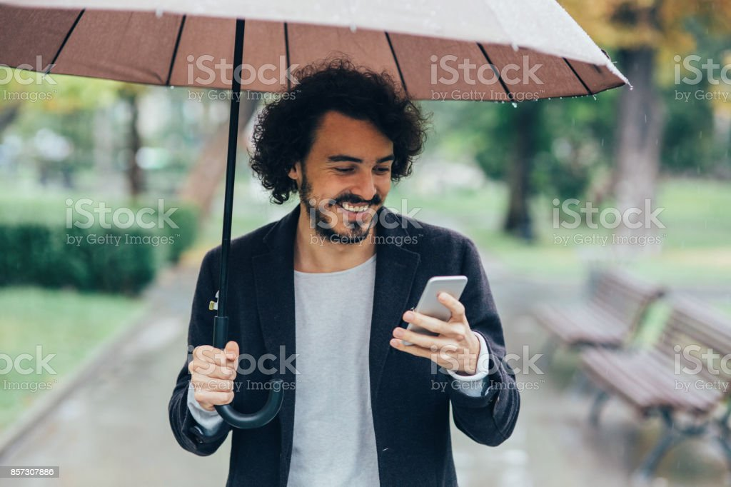Man with an umbrella using a smart phone outdoors.