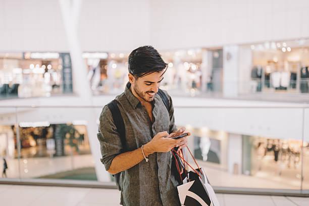 man texting in the shopping mall - online shopping imagens e fotografias de stock