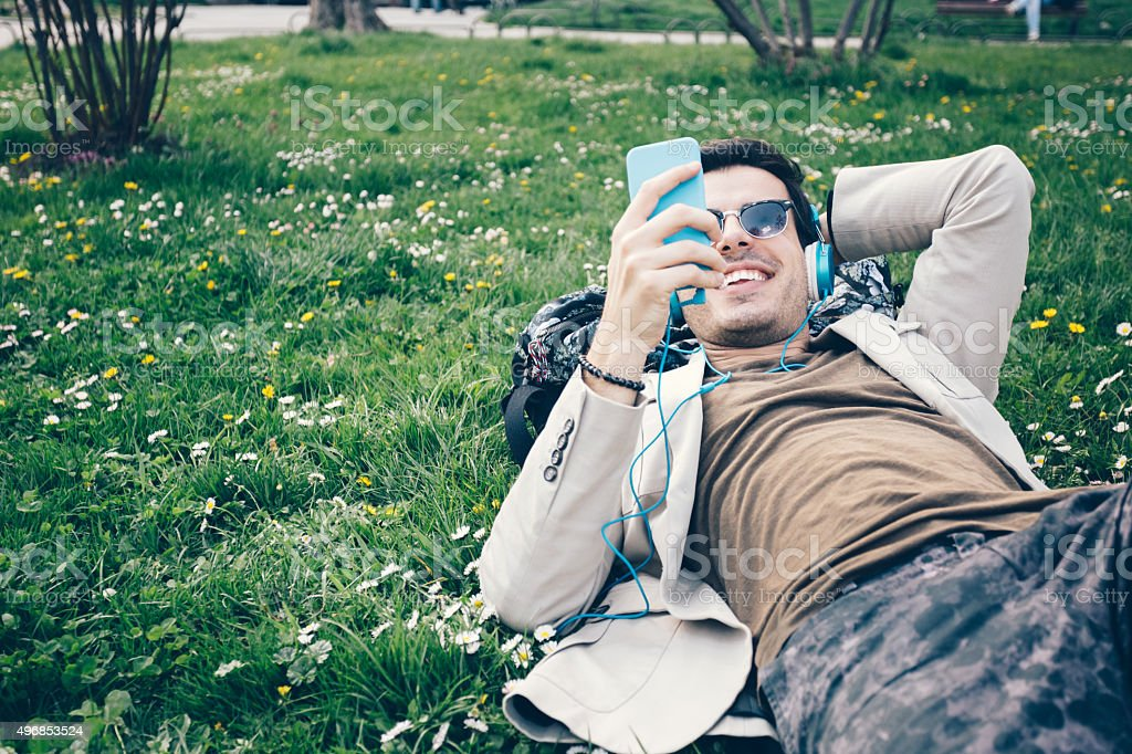 Man texting on cell phone in the park stock photo