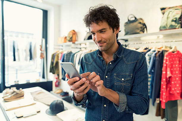 Man texting on cellphone in clothing store stock photo