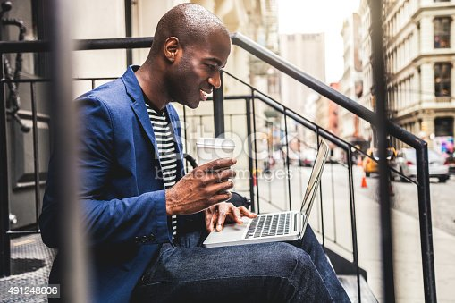 istock Man texting on laptop seated on steps on the streets 491248606