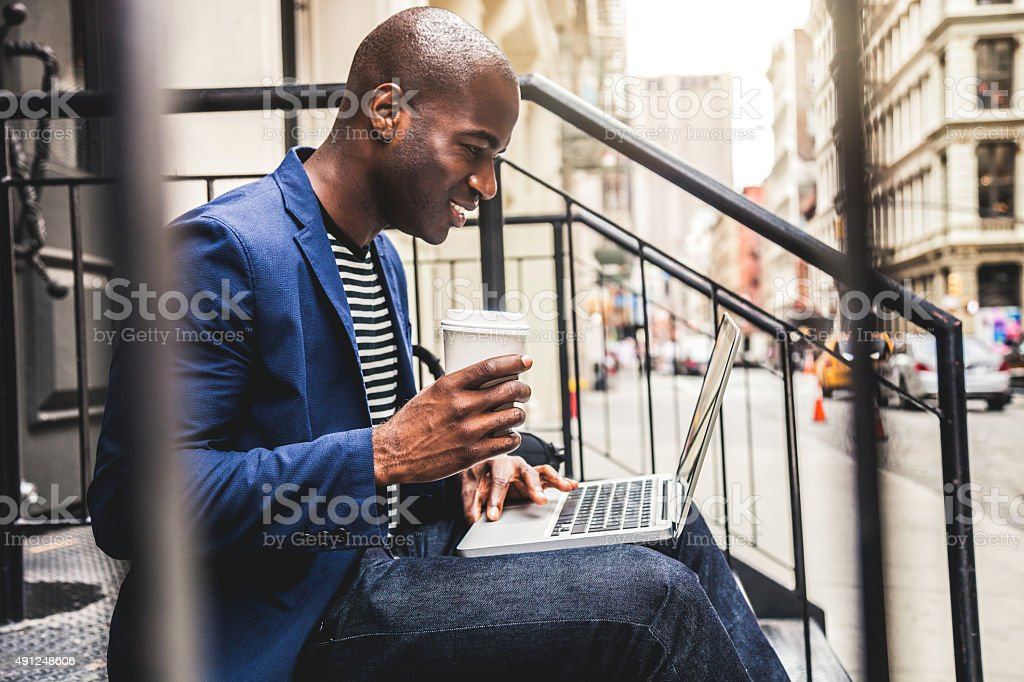 Man texting on laptop seated on steps on the streets stock photo