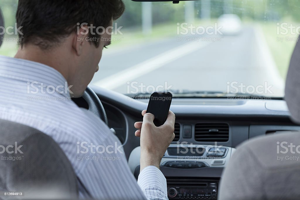 Man texting on mobile phone during driving a car stock photo