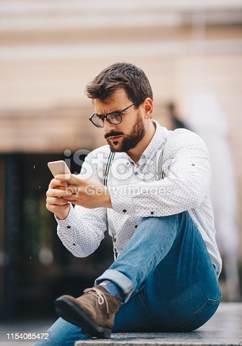 825083556istockphoto Man texting on phone 1154085472